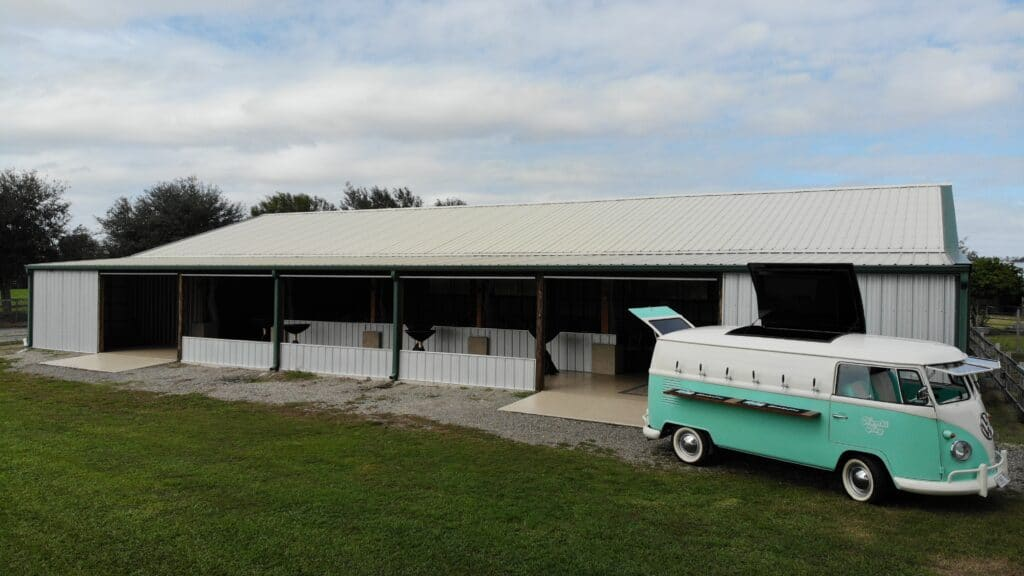 teal and white mobile bar vw van set up outside white barn